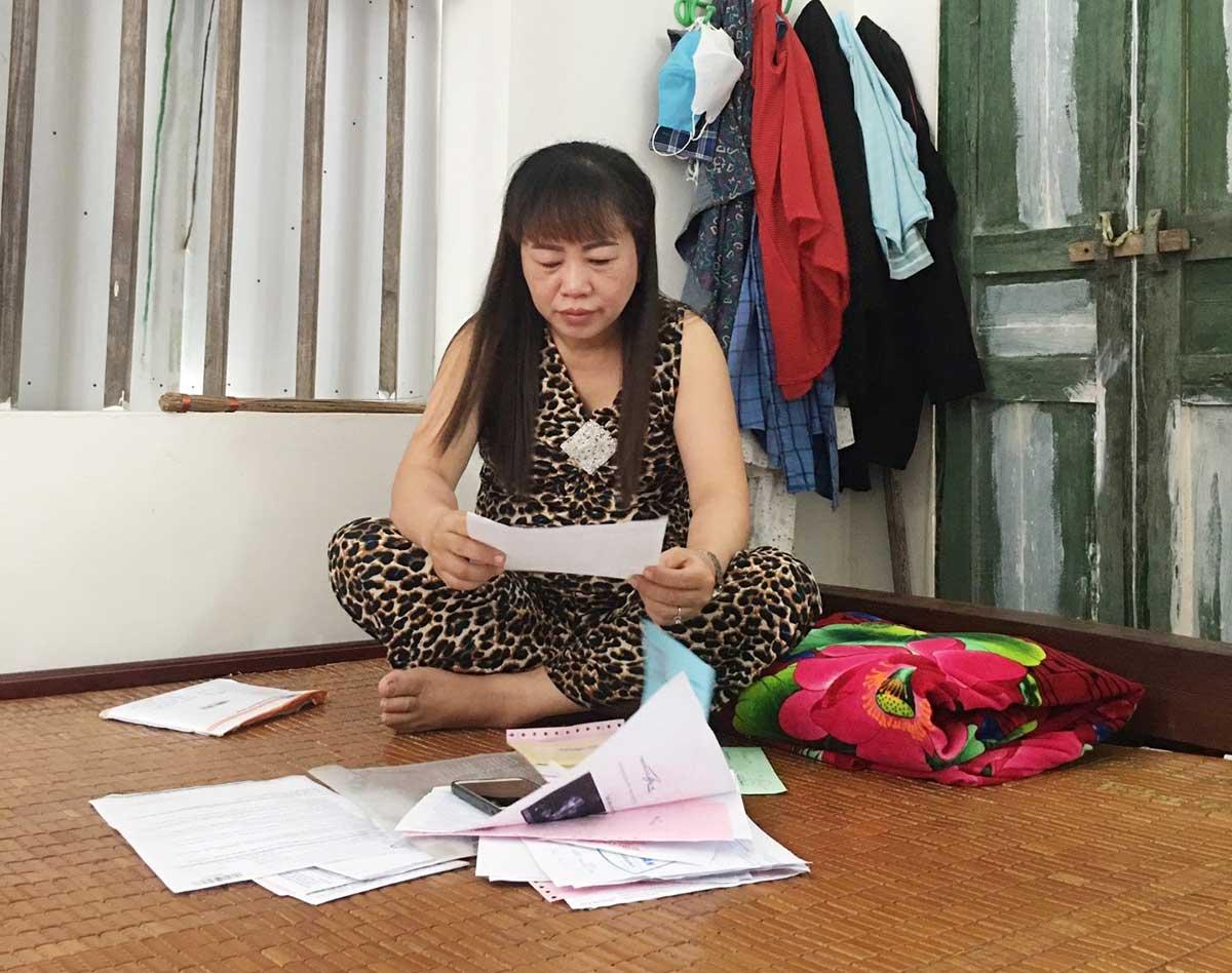 Chị Lụa rưng rưng nước mắt khi xem lại hồ sơ bệnh án của mình